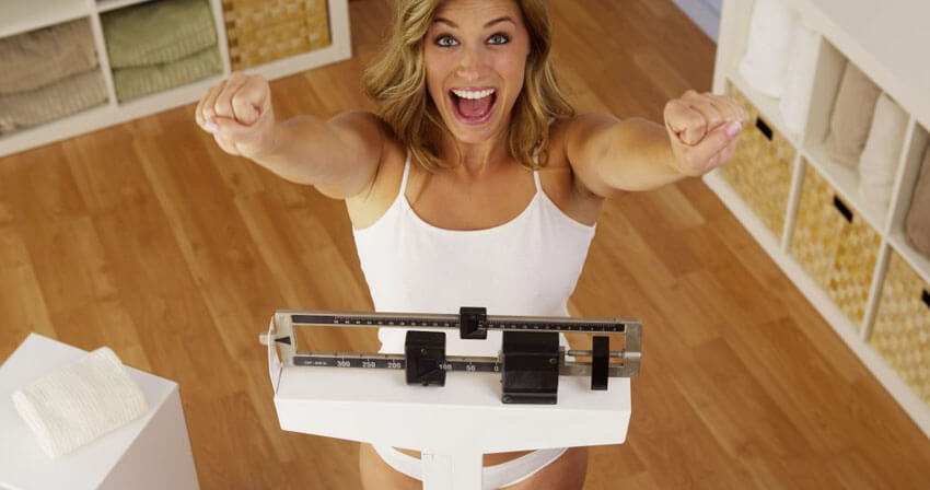 happy woman celebrating healthy fat loss